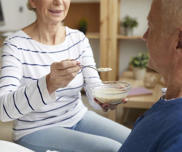 mujer dando de comer a anciano nutricion en geriatria TALIMENT